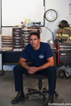 Picture of a Latino fireman sitting in office at the fire station.  Hot Latino fireman sitting on a roll around chair looking sexy.  The ruggedly good looking fire fighter is in his fire uniform, a blue shirt and black pants.